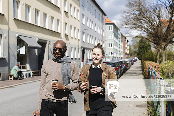 Smiling friends holding coffee cups while walking in city on sunny day