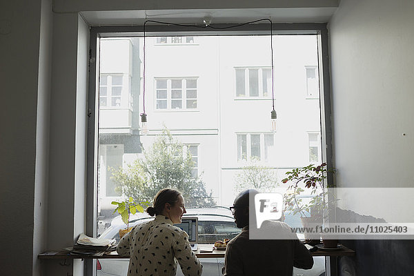 Rear view of happy business people in meeting at coffee shop