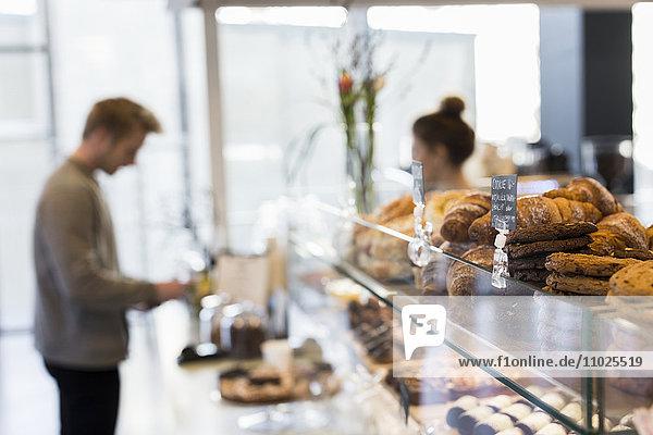 Employee in coffee shop taking order from customer