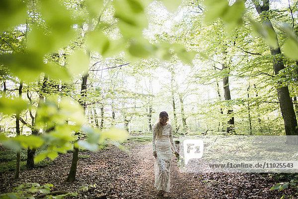 Beautiful bride walking in forest Beautiful bride walking in forest