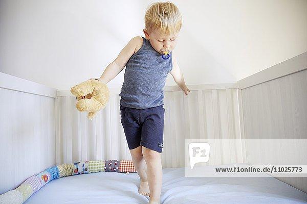 Blonder Junge hüpft im Bett