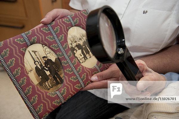Seniorin betrachtet Fotos im Seniorenheim