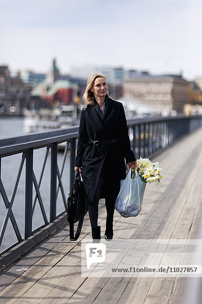 Woman walking with daffodils in shopping bag
