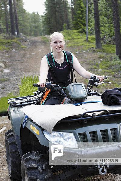 Smiling woman driving four-wheeler