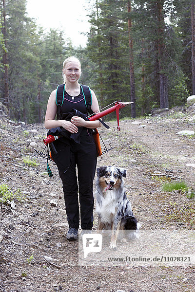 Smiling young woman with dog in forest