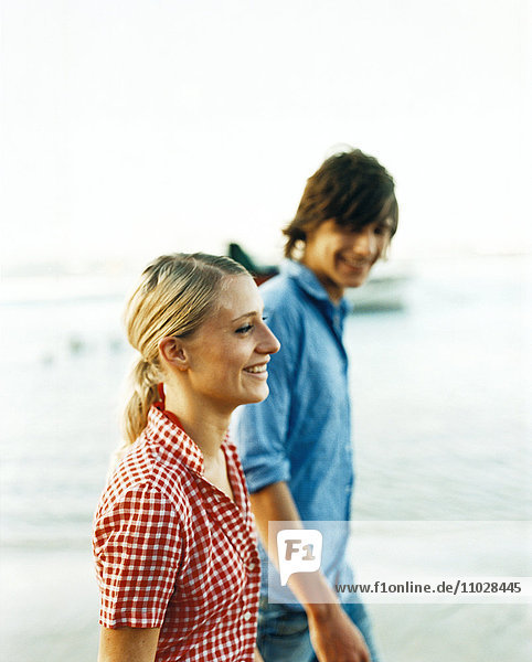 A smiling young couple walking by the sea.