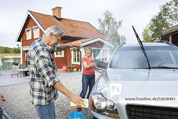 A couple washing their car outside their house.