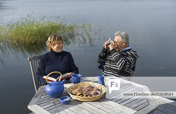 A man photographing a woman  sitting by a table outdoors  having tea.