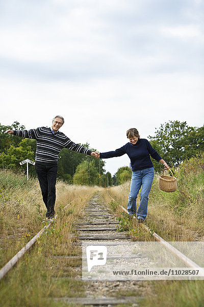 A couple holding hands  balancing on a railway track.
