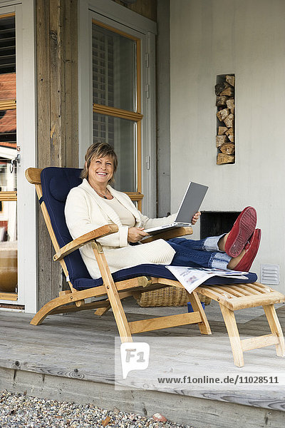 A woman in a sun chair with a laptop.