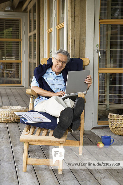 A man sitting in a sun chair with a laptop.