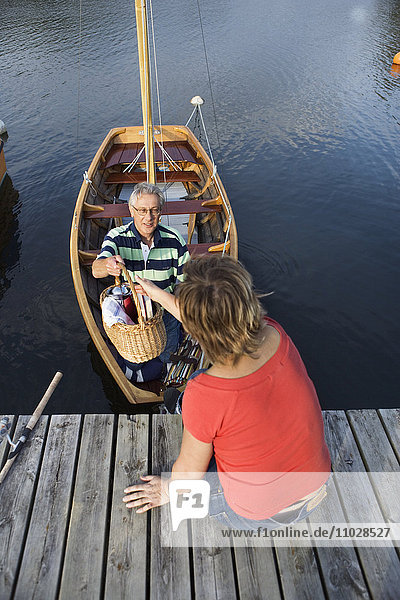 A couple on their way out for a picnic in a boat.