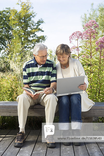 A woman and a man on a bench outdoors with a book and a laptop.