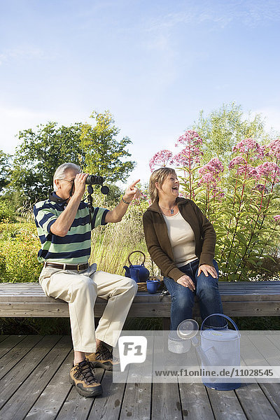 A man looking in a pair of a binoculars and pointing  a woman laughing.