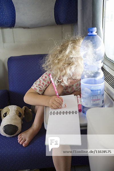 Italy  blonde girl drawing in train