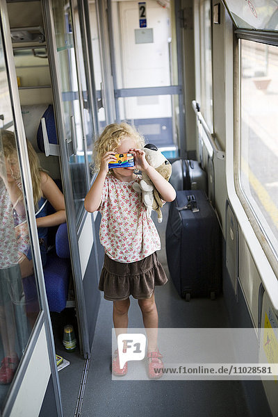 Italy  girl (4-5) taking picture inside train