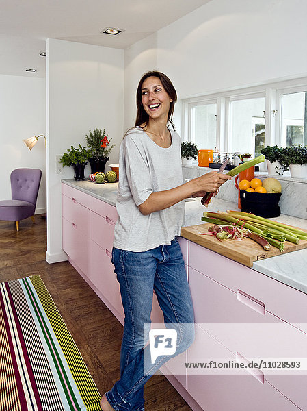 Scandinavia  Sweden  woman smiling while preparing food in kitchen