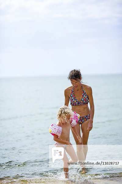 Blonde girl with mother walking on waters edge