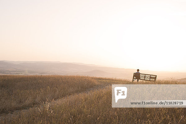 Silhouette of man sitting on bench
