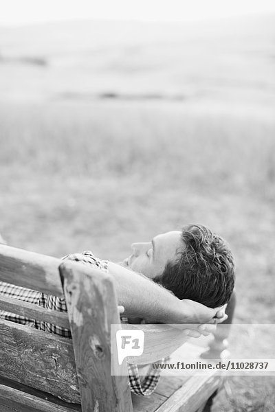 Mid adult man relaxing on bench
