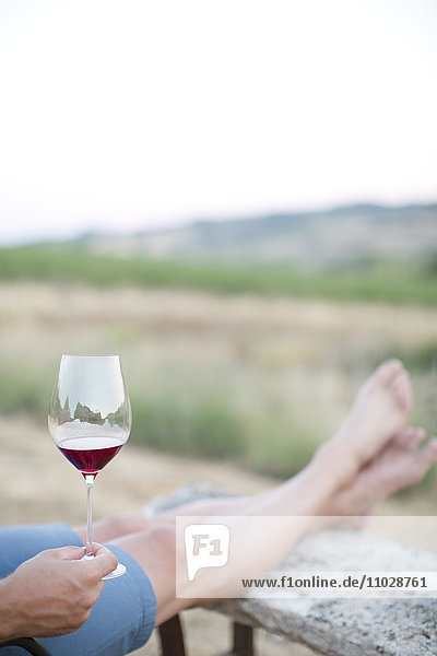 Mid adult man relaxing with wine  low section