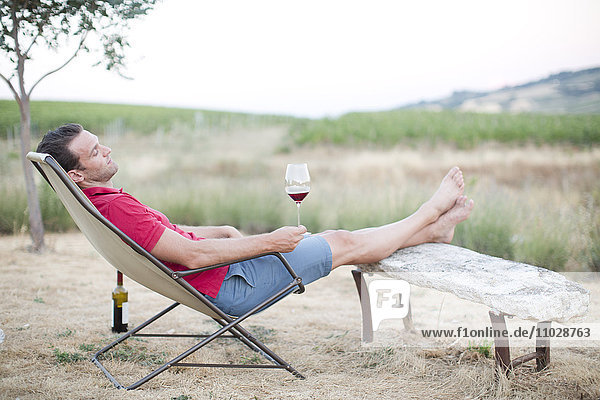 Mid adult man relaxing on sun chair