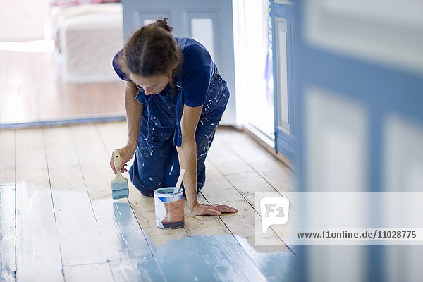 Woman painting wooden floor