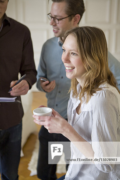 Young businesswoman laughing over cup of coffee with colleagues in background