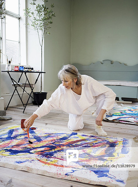 A woman painting on the floor.