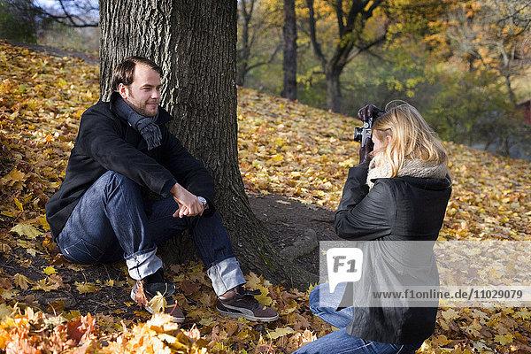 A woman that photographs a man outdoors.