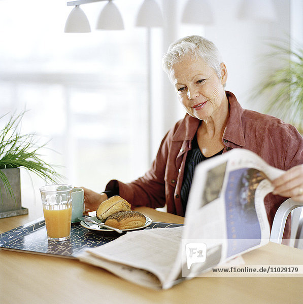 A woman eating breakfast and reading a newspaper.