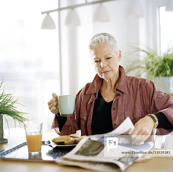 A woman eating breakfast and reading newspaper.