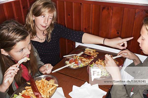 Three girls eating chips in restaurant