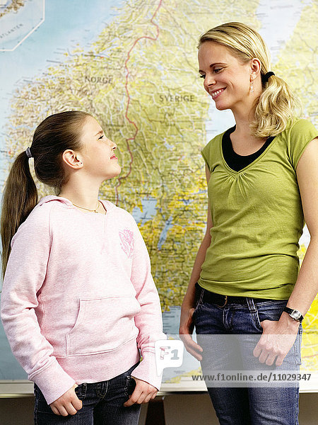 Pupil and teacher in front of map.
