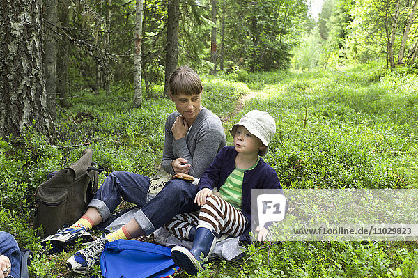 Mother and son having break in forest