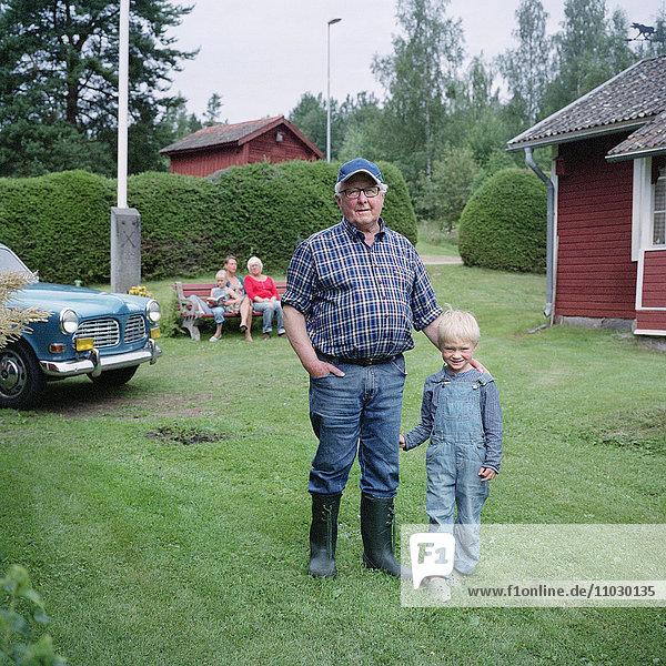 Senior man standing with grandson,  children in background