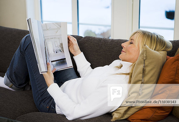 Woman lying on couch and reading