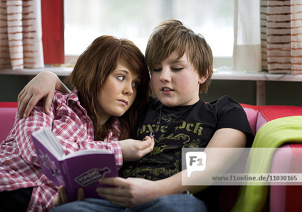 Teenage boy and girl on sofa reading book