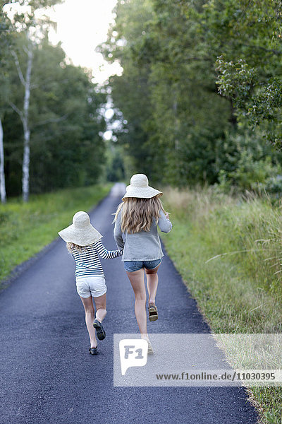 Two sisters running together on country road