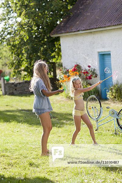 Girls making bubbles in garden