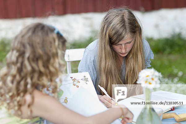 Girls doing homework outside
