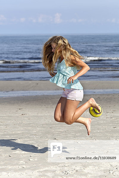 Teenage girl jumping on beach