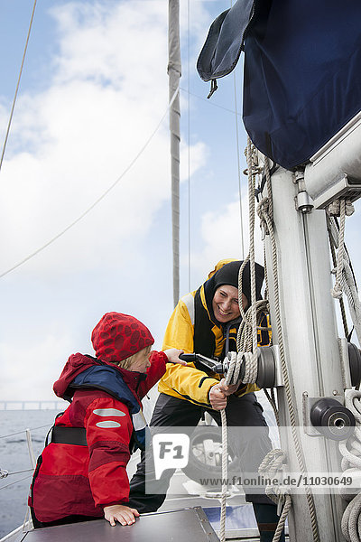 Mother and daughter winding rope on sailing boat  smiling