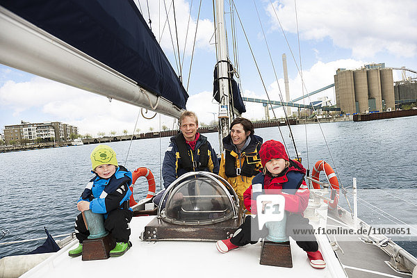 Family sitting in sailing boat,  smiling