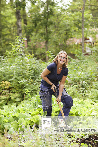 Smiling mature woman digging in garden