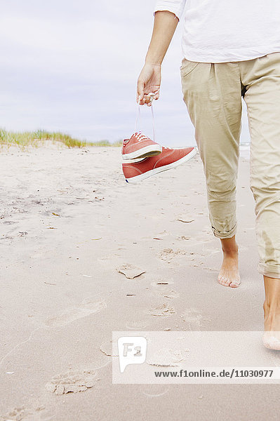 Woman on beach carrying shoes  close-up