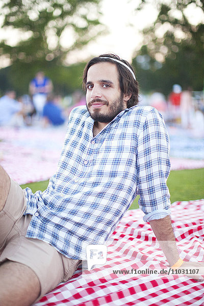 Smiling young man sitting in park  New York City  USA