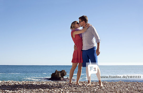 Young couple on beach kissing