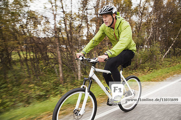 Mature man setting riding mountain bike along country road