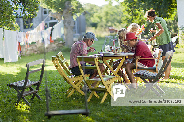 Family dining at outdoor table in garden